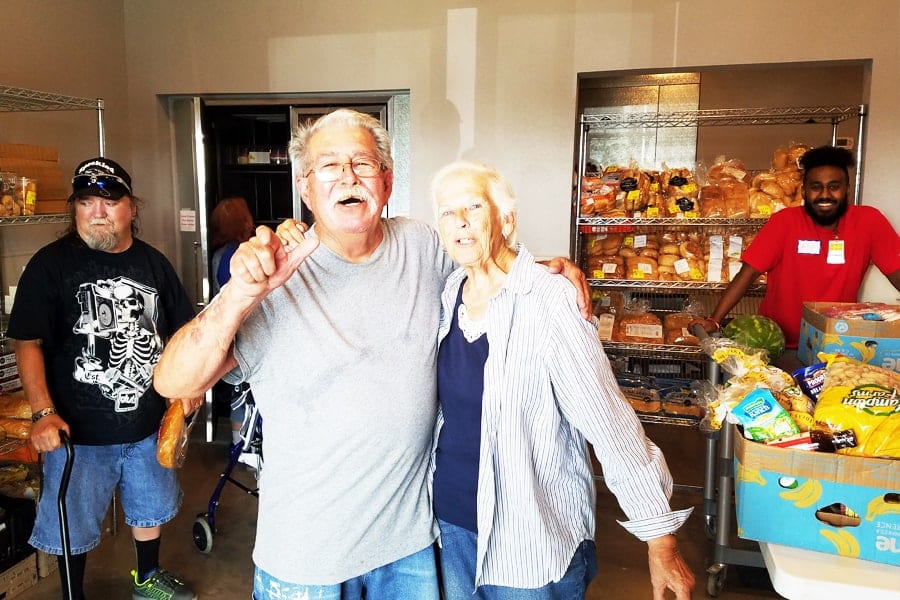 Ted and Carol receiving food at Amazing Grace